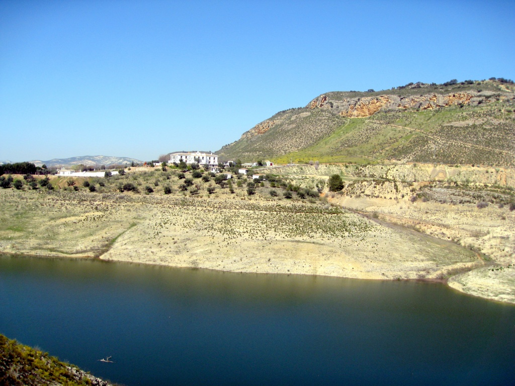 reservoir with steep banks and olive trees around it.