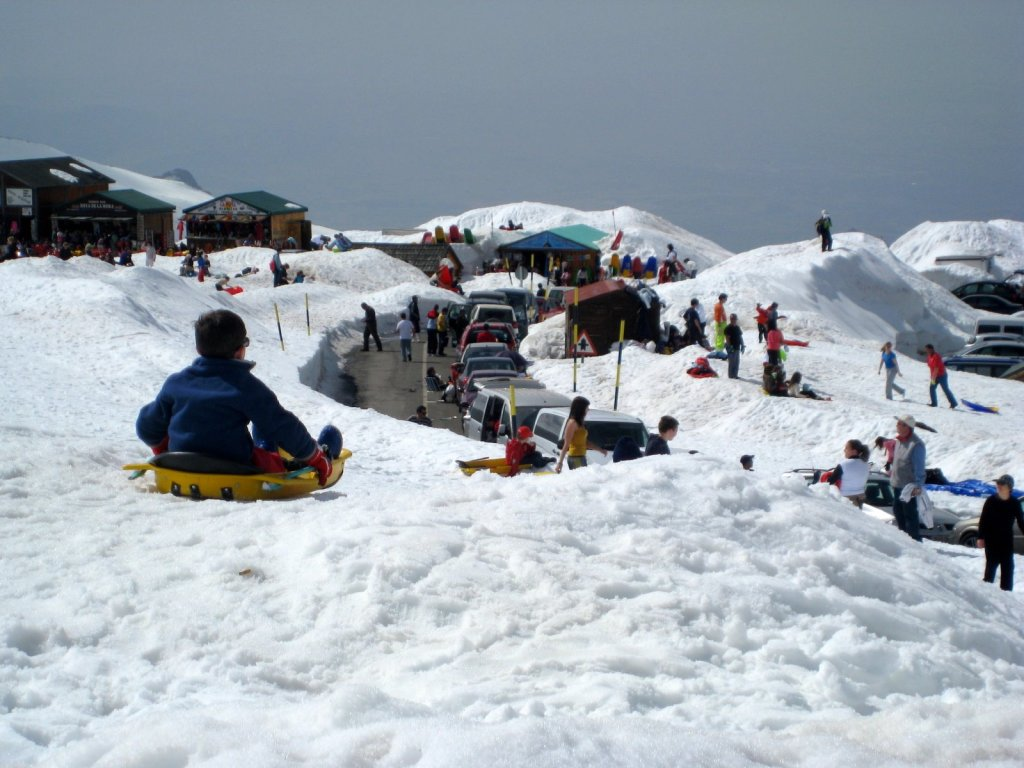 kid sledding on a snow bank above a road with parked cars and people.