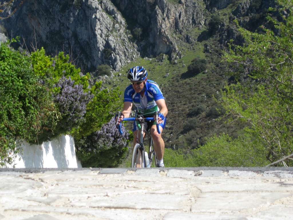 cyclist coming up up a steep hill to a flat section with beautiful green mountain behind.