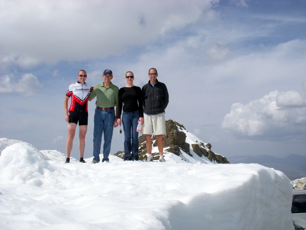 four people standing on a high snow bank with a mountain behind.