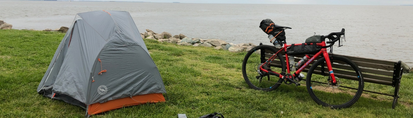 A bike and tent on the lawn by the bay